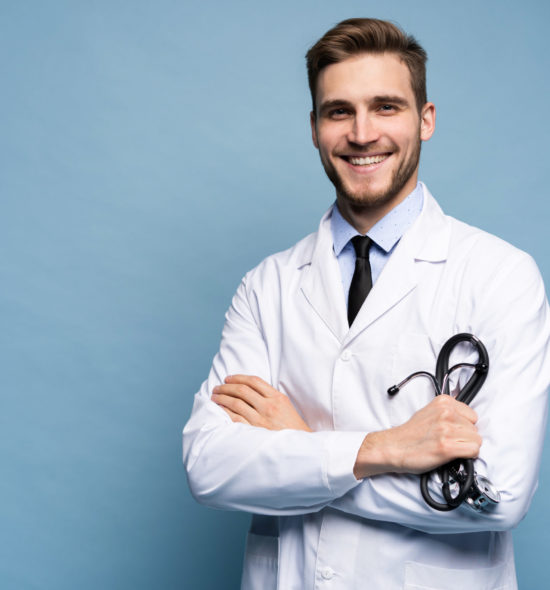 Portrait of confident young medical doctor on blue background